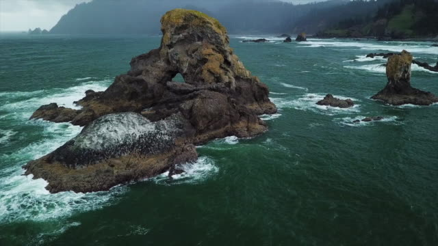aerial pan left to right: rock formation on the waters of cannon oregon - cannon beach stock videos & royalty-free footage