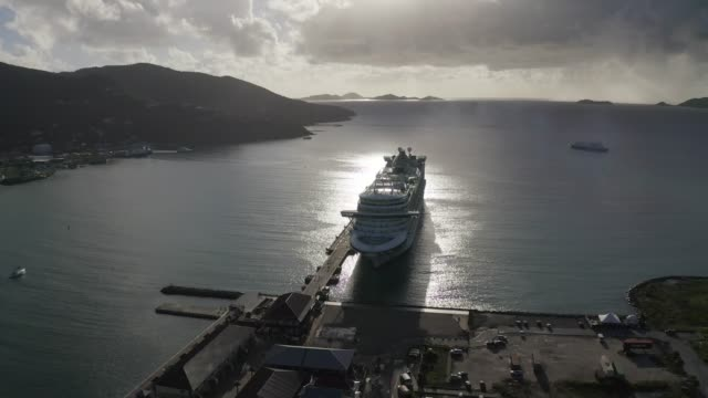 aerial pan left to right: sun shining on the waters of dock and cruise ship - cruising stock videos & royalty-free footage