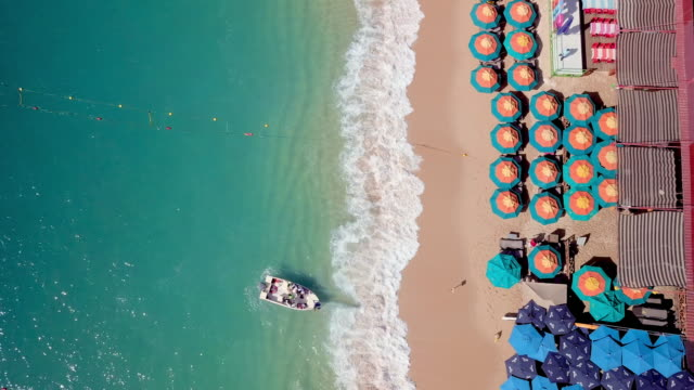 aerial pan left to right: waves and umbrellas - cabo san lucas stock videos & royalty-free footage