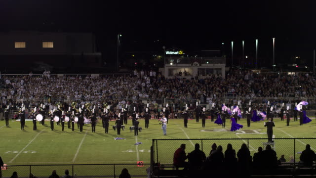 aerial pan of high school band performing - marching band stock videos & royalty-free footage