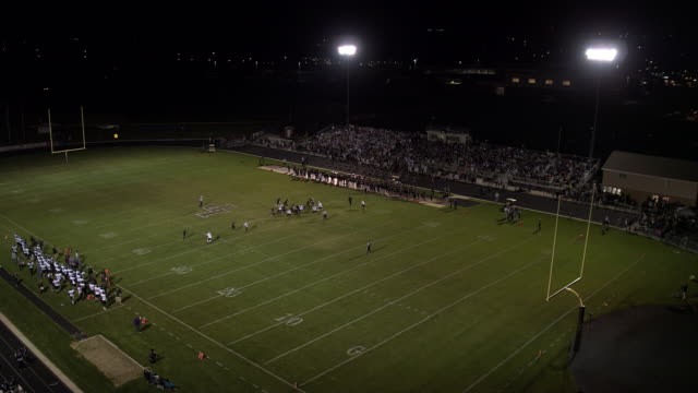aerial pan of high school football game at night - match sport stock videos & royalty-free footage