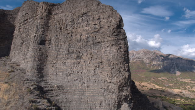 aerial pan of rocky cliff revealing mountain - felswand stock-videos und b-roll-filmmaterial