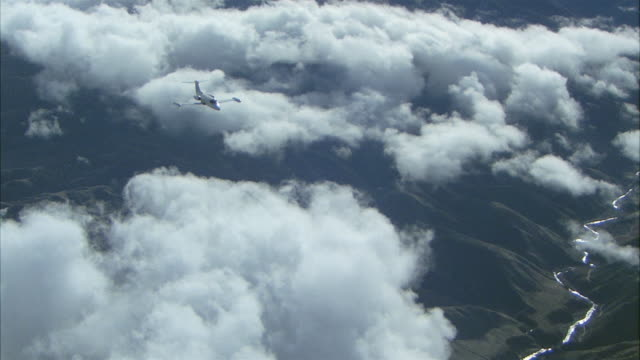 aerial pan private jet flying above clouds over mountain range - air to air shot stock videos & royalty-free footage