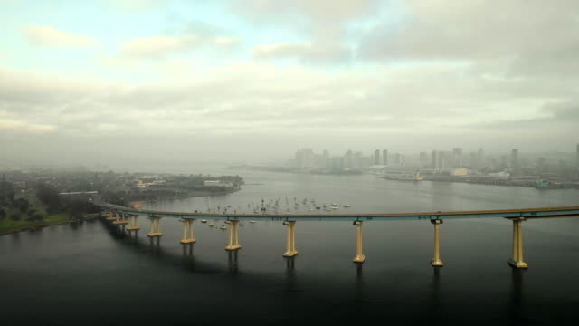 stockvideo's en b-roll-footage met aerial pan right: thin bridge leading into city on cloudy day in san diego, united states of america - san diego