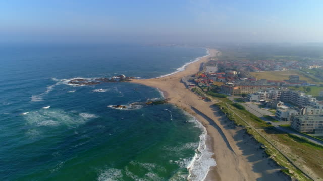 aerial pan right to left: magnificent view of city beach of porto portugal with strong waves in the alluring area - porto district portugal stock videos & royalty-free footage