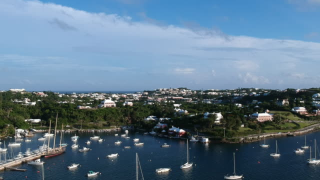 aerial pan right to left: the coastline of bermuda full of boats and homes in spanish point, bermuda - 大西洋諸島点の映像素材/bロール