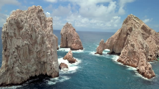 aerial pan right to left: view of arch at lovers beach in cabo san lucas - 石灰岩点の映像素材/bロール
