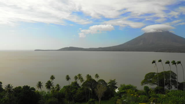 aerial pan right: trees on edge of ocean with volcano, smoke on opposite side - ometepe, nicaragua - nicaragua stock videos & royalty-free footage