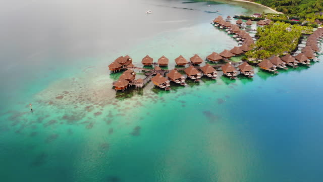 aerial pan right: tropical vacation homes in ocean in bora bora, french polynesia - bora bora aerial stock videos and b-roll footage
