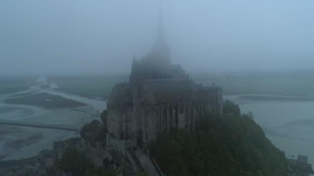 vidéos et rushes de aerial pan: romanesque abbey at peak of mont saint-michel in fog at dusk - normandy, france - moyen âge