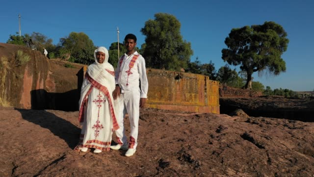 stockvideo's en b-roll-footage met aerial pan shot of a couple in front of the monolithic rockcut church of saint george dated to the late 12th amhara region lalibela ethiopia on... - hoorn van afrika