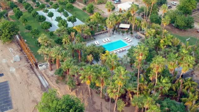 aerial pan: swimming pool in a beautiful estate - utebassäng bildbanksvideor och videomaterial från bakom kulisserna