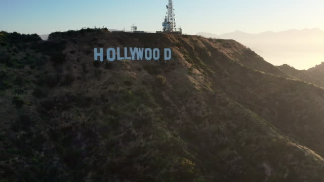 aerial pan: the hollywood sign and mountainous terrain on sunny day in hollywood - hollywood, california - santa monica los angeles video stock e b–roll