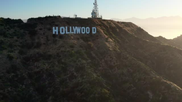 vídeos y material grabado en eventos de stock de aerial pan: the hollywood sign and mountainous terrain on sunny day in hollywood - hollywood, california - símbolo