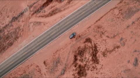 aerial pan up: cars driving down road in middle of desert plain in monument valley, ut - mittdel bildbanksvideor och videomaterial från bakom kulisserna