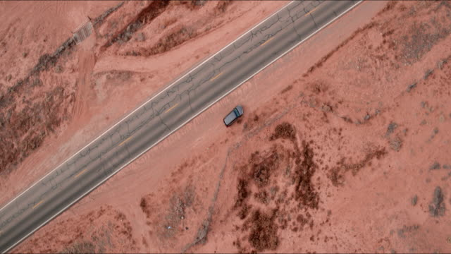 aerial pan up: cars driving down road in middle of desert plain in monument valley, ut - mittlerer teil stock-videos und b-roll-filmmaterial