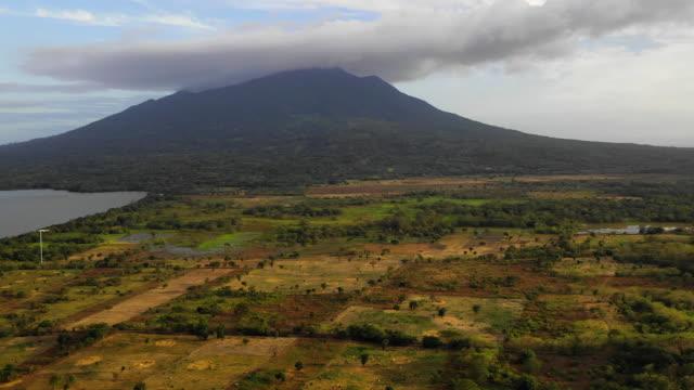stockvideo's en b-roll-footage met aerial pan up: green valley around dark volcano, smoke above - ometepe, nicaragua - watervorm