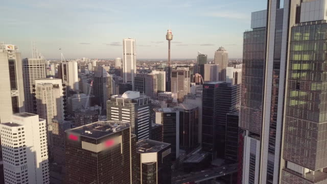 aerial pan up/left: tall sydney city buildings on a sunny, clear day, sydney, australia - downtown stock videos & royalty-free footage