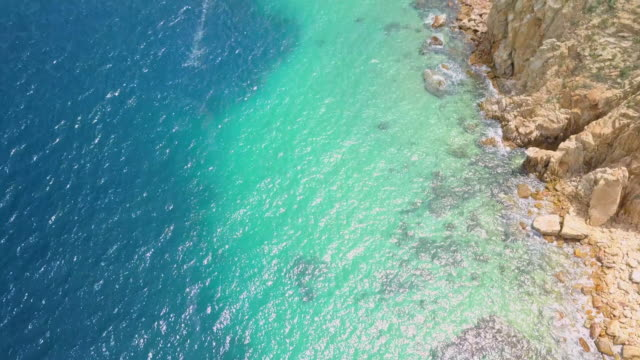 aerial pan upward: clear waters of mexico cliffs - cabo san lucas stock videos & royalty-free footage