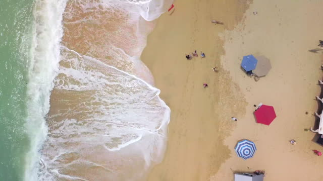 aerial pan upward: the wet sand of medano beach mexico - cabo san lucas stock videos and b-roll footage
