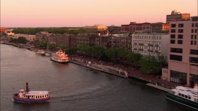 aerial pan waterfront district and boats at dusk/ savannah, georgia - georgia stati uniti meridionali video stock e b–roll