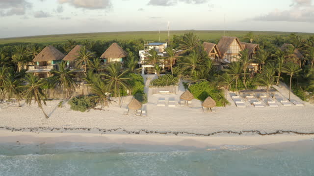 aerial panning a beautiful caribbean beachside resort with crashing waves, swaying palm trees, and lush green landscape - tulum, mexico - tourist resort stock videos & royalty-free footage