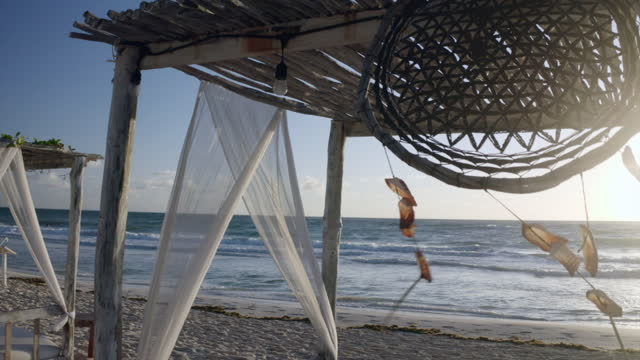 aerial: panning a dreamcatcher hanging from a resort beach cabana and swaying in the ocean breeze with bright direct sunlight and gentle caribbean waves - tulum, mexico - exklusiv stock-videos und b-roll-filmmaterial