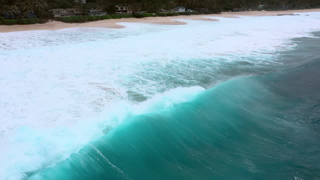 aerial panning a group of apt surfers paddling and surfing giant crashing waves with deep blue ocean water and white foaming surf along a beach - oahu, hawaii - overcast stock-videos und b-roll-filmmaterial