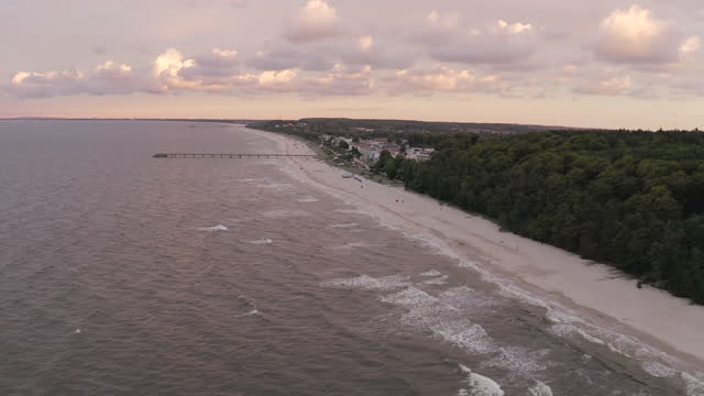 aerial panning a quiet baltic sea beachfront and small coastal town with warm sunlight, gentle waves, and cloudy skies - usedom, germany - town stock videos & royalty-free footage