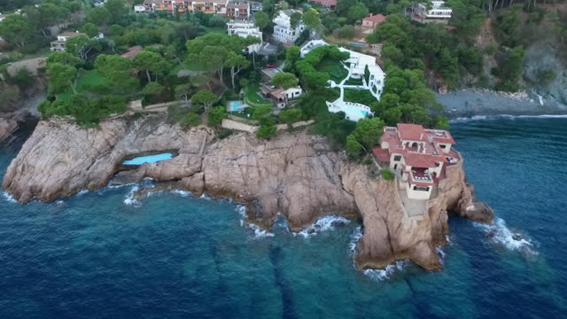 aerial panning: beach and blue sea near villas on rock formations - begur, spain - island stock videos & royalty-free footage