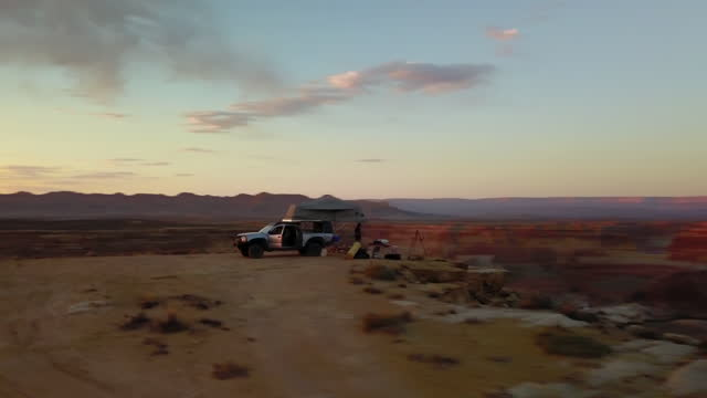 aerial: panning beautiful shot of camper van and person at national park with river during sunset - page, arizona - canyon stock videos & royalty-free footage