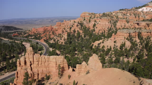 aerial panning canyon walls and hillsides, with hoodoos, bright blue sky, pine trees, and the canyon rock formations stretching into the background - bryce, utah - ブライス峡谷点の映像素材/bロール