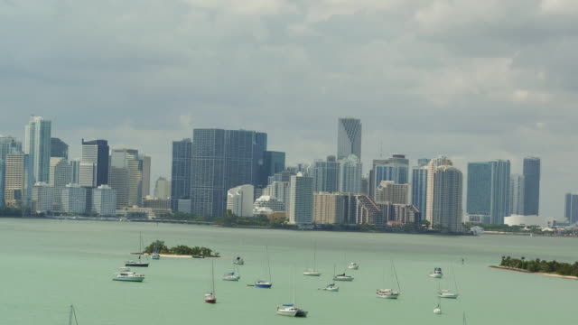 aerial panning down from miami skyline over a small island and boats anchored in the ocean - anchored stock videos & royalty-free footage