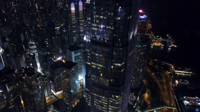 Aerial: Panning Down Skyscraper in Hong Kong City at Night