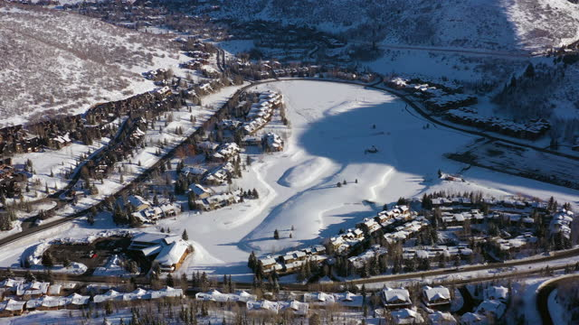aerial panning high above residential neighborhood in a snowy mountain ski town with quiet streets and bright morning sunlight - park city, utah - park city stock videos & royalty-free footage