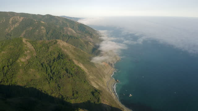 aerial panning high above the clouds and over the steep mountain shoreline along the pacific ocean coast, with bright sunlight, deep blue ocean waters, and the green brush - big sur, california - aerial stock videos & royalty-free footage