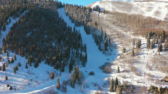 aerial panning hillside ski trails and residential neighborhood in a snowy mountain ski town with quiet streets and bright morning sunlight - park city, utah - park city stock videos & royalty-free footage