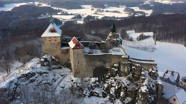 aerial panning historic bavarian hohenstein castle high on a hill and surrounded by a snowy winter landscape with rolling hills and forest trees - festung stock-videos und b-roll-filmmaterial
