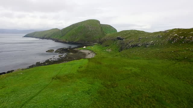 vidéos et rushes de aerial panning low across ancient rock formations and sheep on a remote scottish island, with green grass, a rugged shore, and dark blue ocean waters under a cloudy gray sky - shiant isles, united kingdom - scottish culture