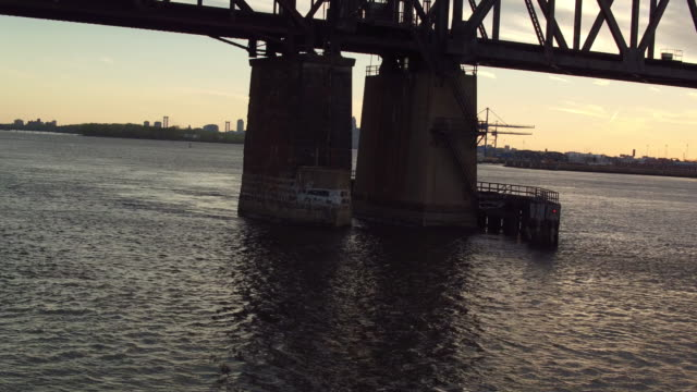 aerial panning low over water under a railroad bridge on the delaware river - デラウェア川点の映像素材/bロール