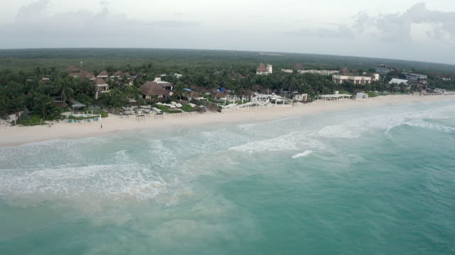 aerial panning luxury beachside condo homes and resorts on the yucatan peninsula, with lush green palms and gentle caribbean ocean waves - tulum, mexico - bay of water stock videos & royalty-free footage