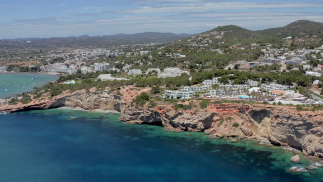 aerial: panning on tourist resort on cliff by sea during sunny day - ibiza, spain - イビサ島点の映像素材/bロール
