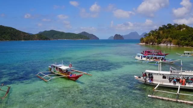 aerial: panning over banca boats anchored and blue ocean in palawan, philippines - anchored stock videos & royalty-free footage