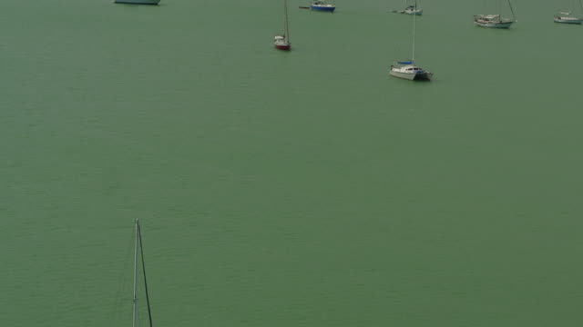 aerial panning over boats anchored in a green ocean before the miami skyline - anchored stock videos & royalty-free footage