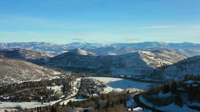 aerial panning over residential neighborhood in a snowy mountain ski town with quiet streets and bright morning sunlight - park city, utah - park city stock videos & royalty-free footage