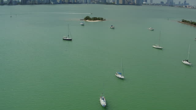 stockvideo's en b-roll-footage met aerial panning over sailboats and motorboats in a light green sea in front of miami skyline - voor anker gaan