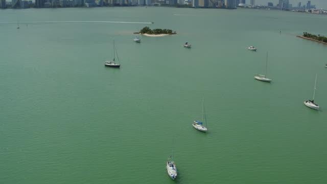 aerial panning over sailboats and motorboats in a light green sea in front of miami skyline - ankrad bildbanksvideor och videomaterial från bakom kulisserna