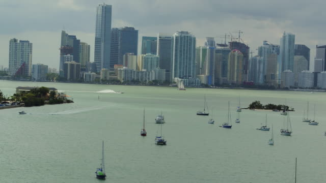 vídeos de stock e filmes b-roll de aerial panning over the ocean in front of the miami skyline on a spring afternoon - ancorado