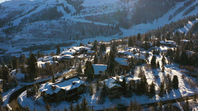 aerial panning residential neighborhood in a snowy mountain ski town with quiet streets and bright morning sunlight - park city, utah - park city stock videos & royalty-free footage