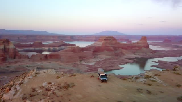 aerial: panning scenic view of vehicle parked on top of mountain during sunset - page, arizona - canyon stock videos & royalty-free footage